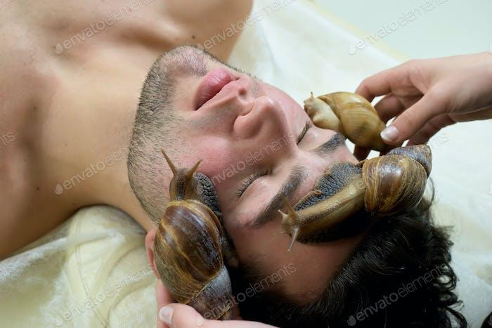 Young man receiving snails massage
