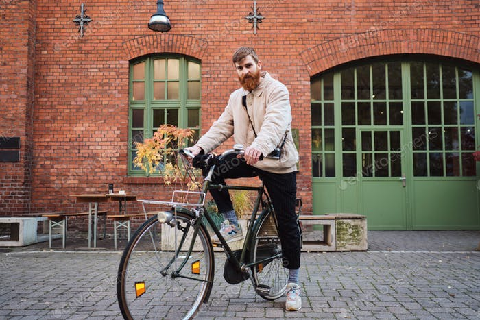 Young attractive bearded man thoughtfully looking in camera with old classic bicycle on city street