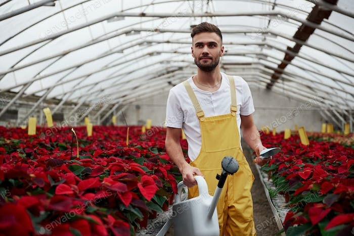 Having a distant look. Portrait of beautiful young guy in the hothouse taking care of flowers