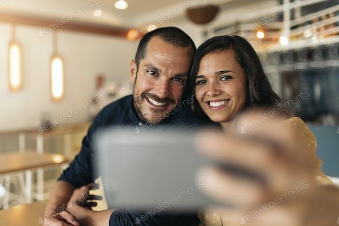 Happy couple taking selfie.