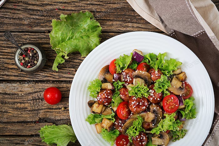 Salad with meatballs, eggplant, mushrooms and tomatoes in Asian style.