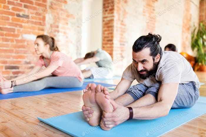 group of people doing yoga forward bend at studio
