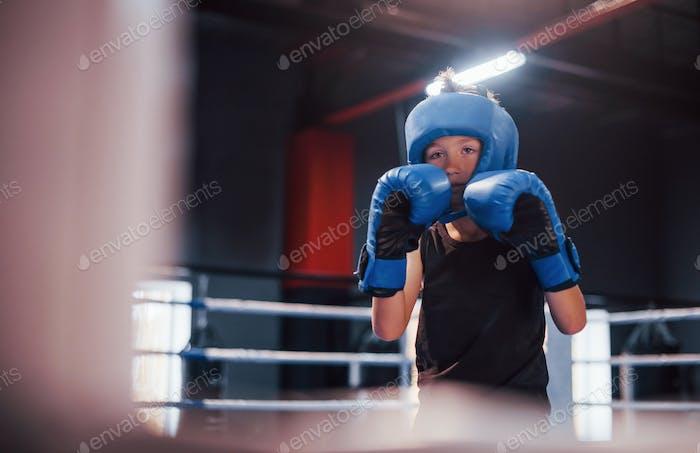 Junge in sportlicher Schutzausrüstung steht auf dem Boxring und macht Übungen