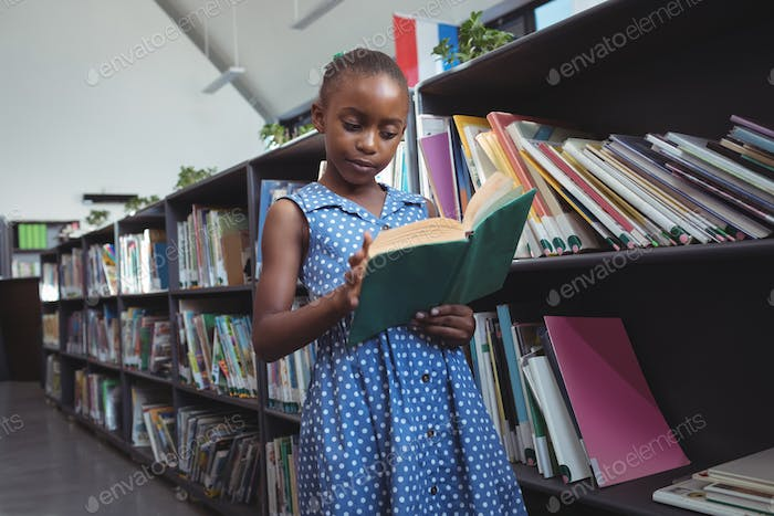 Girl reading book by bookshelf in library