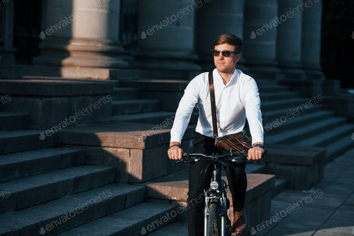 In sunglasses. Businessman in formal clothes with black bicycle is in the city