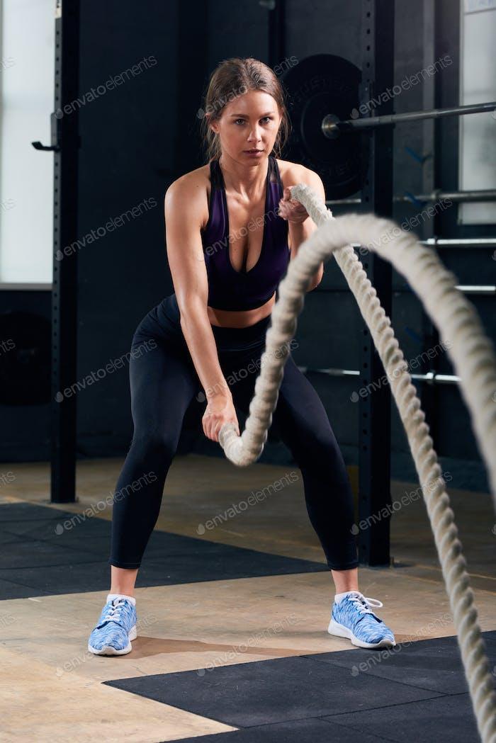 Junge Frau Training mit Kampfseilen im Fitnessstudio
