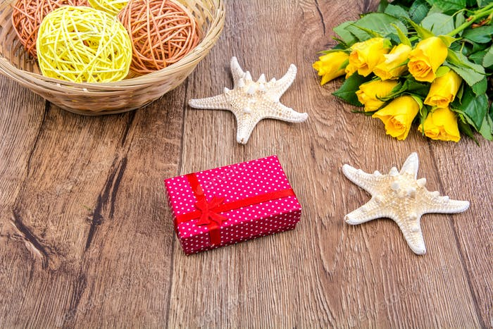Starfishes, gift and roses on a wooden table