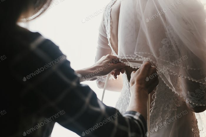 Mother hands holding ribbons and helping dressing beautiful bride in morning