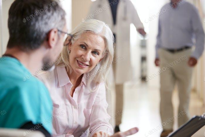 Arzt Begrüßung zu Senior Female Patient wird in Krankenhaus aufgenommen
