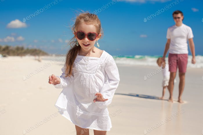 Забавный старшая дочь на переднем плане и папа с младшей дочерью в фоновом режиме на пляже