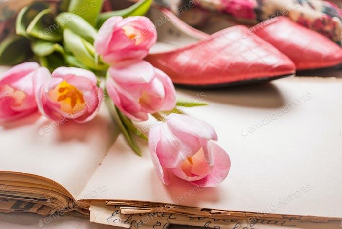 Rosa Tulpen und leeres Buch mit Damenschuhen über weißem Holztisch. Nahaufnahme