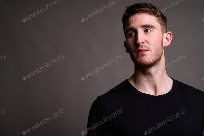 Portrait of young handsome man against gray background