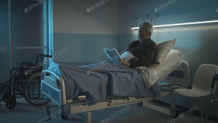 Lonely elderly man reading a book at the hospital