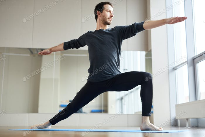 Slim man doing standing yoga pose