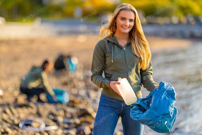 Volunteer holding bottle and garbage bag at beach