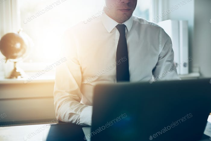 Close up of business man working at laptop