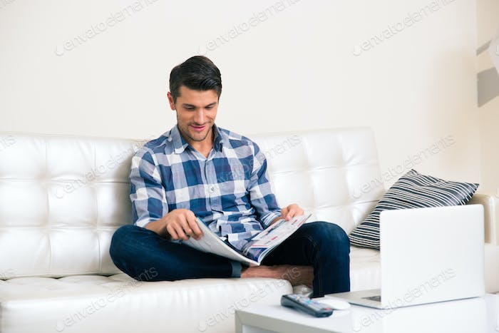 Man reading magazine on the sofa