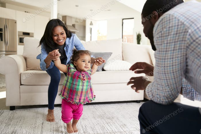 Family At Home Encouraging Baby Daughter To Take First Steps