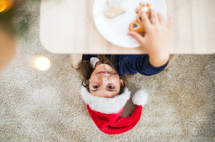 A top view of a small girl with Santa hat reaching for biscuit at Christmas time.