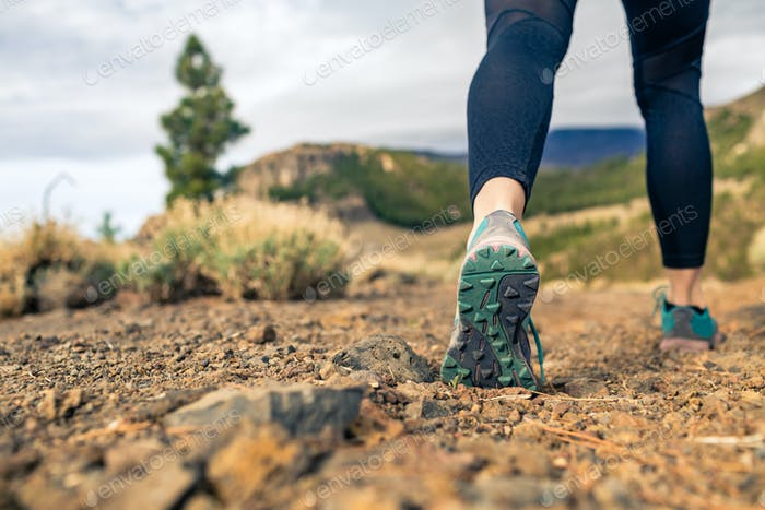 Sole of shoe walking in mountains on rocky footpath