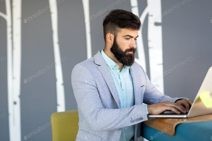 Focused serious businessman in suit thinking reading online news