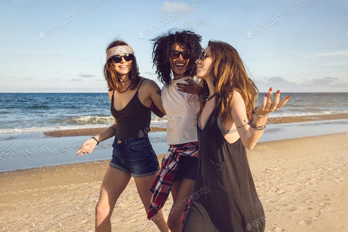 Three friends walking on the beach and laughing