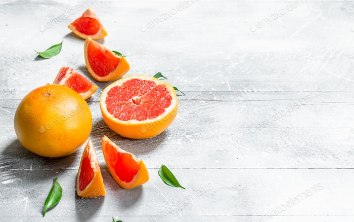 Pieces of grapefruit with leaves.