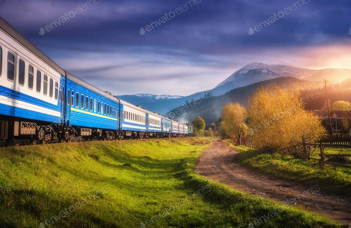 Moving train in mountains at sunset in autumn. Railway station