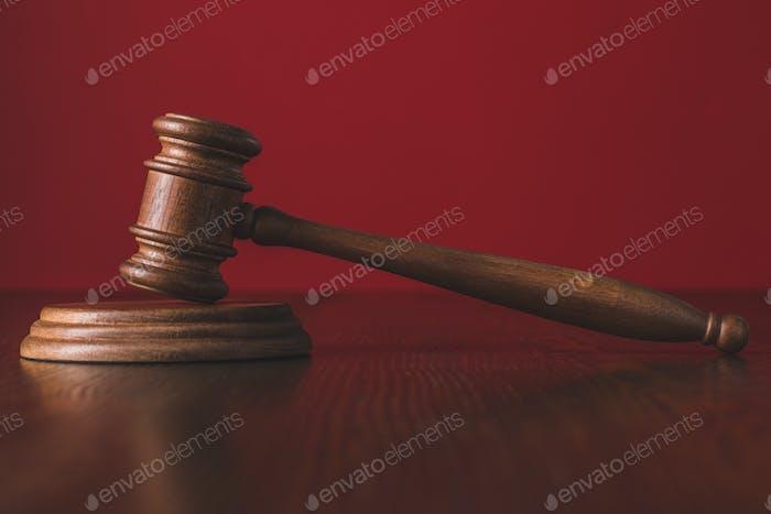 juicios martir en la mesa de madera frente al fondo rojo, concepto de ley