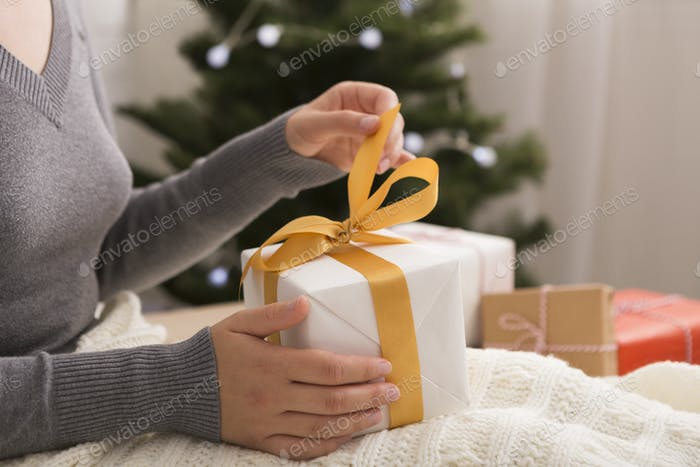 Woman opening gift box at home in cozy Christmas atmosphere