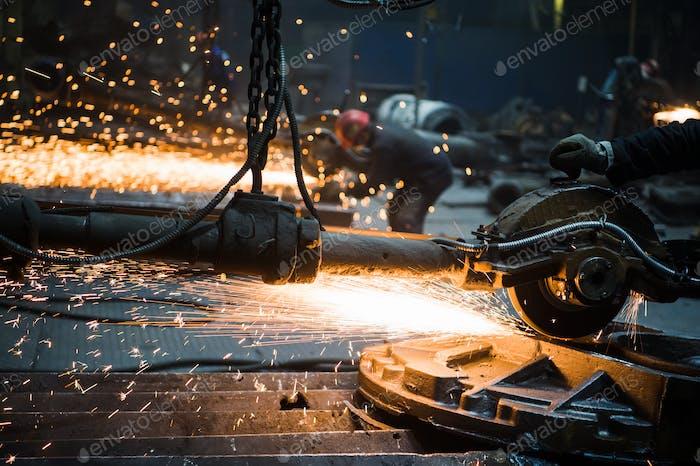 Nahaufnahme der männlichen Arbeiter Hände, tragen spezielle Schutzhandschuhe, Schneiden Metall mit großen elektrischen