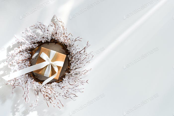 Christmas gift box and wreath branches of frost on white background with sunlight rays, flat lay