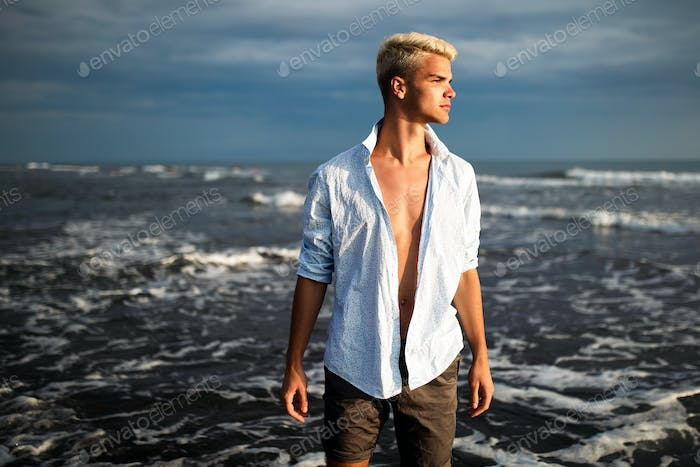 Handsome happy man wearing white shirt at the sea or the ocean background
