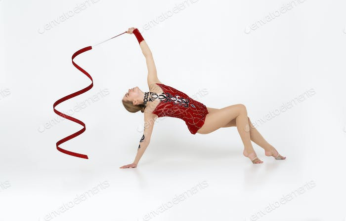 Lovely sportswoman with gymnastic string practicing her dance on white background