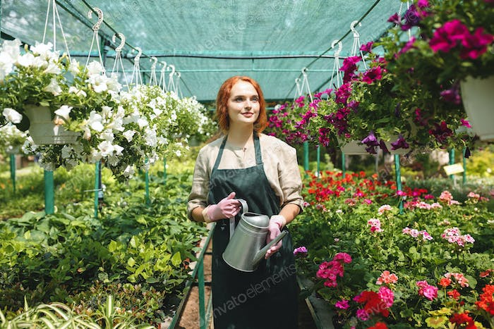Pretty lady in apron standing with watering can in hands around beautiful flowers
