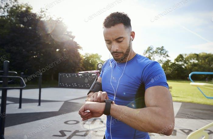 Young man at outdoor gym setting fitness app on smartwatch