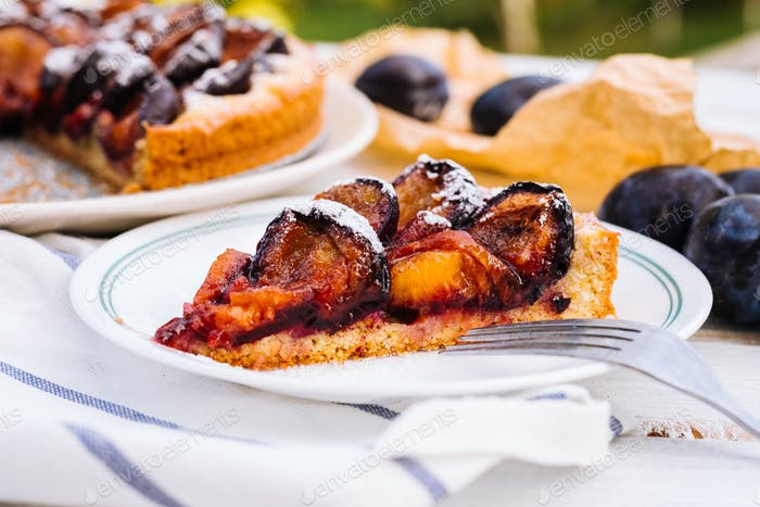 Homemade plum pie on the wooden background