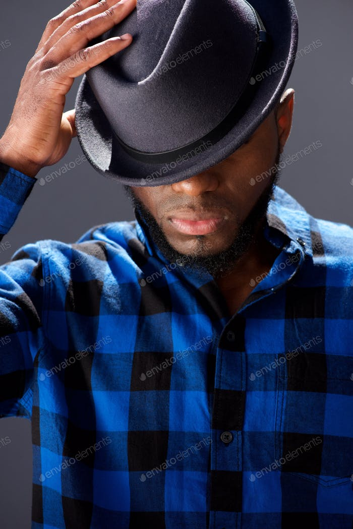 handsome man with hand to hat looking down