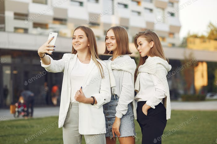 Young students on a student campus with a phone
