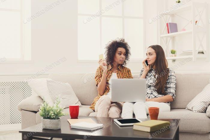 Zwei Frauen online mit Kreditkarte und Laptop