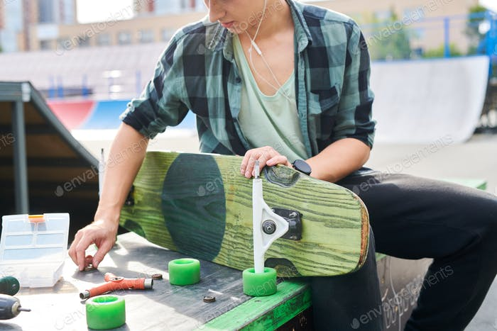 Young Man Fixing Skateboard