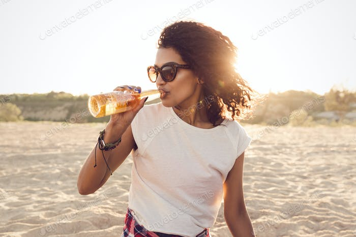 Young pretty african girl in sunglasses drinking beer