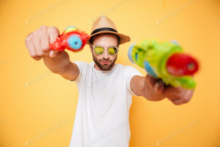Serious young man holding toy water guns.