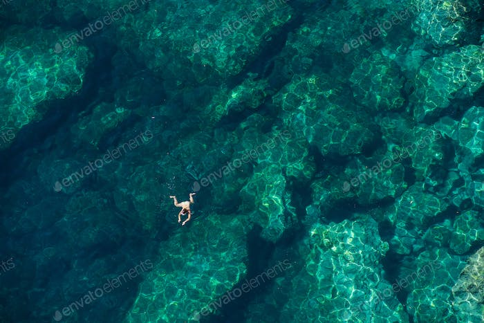 Drone view of a woman snorkeling in the sea. Summer vacation concept