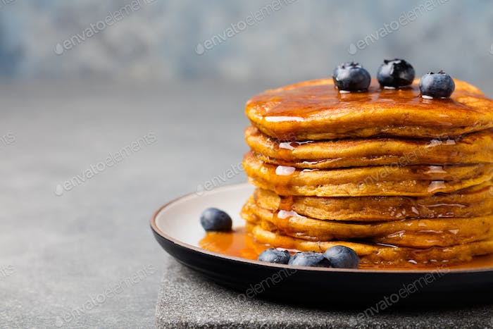 Pumpkin pancakes with maple syrup and blueberries on a plate. Grey stone background