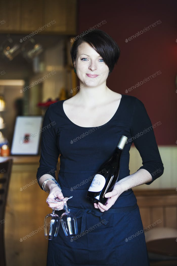 Restaurant staff, a woman in a blue dress holding a bottle and two wineglasses.