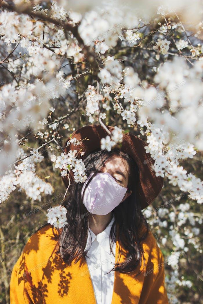 Zarte Blumen und junge Frau entspannen draußen in handgemachte Maske