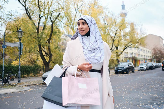 Young attractive Arabic woman in hijab dreamily walking with shopping bags on street