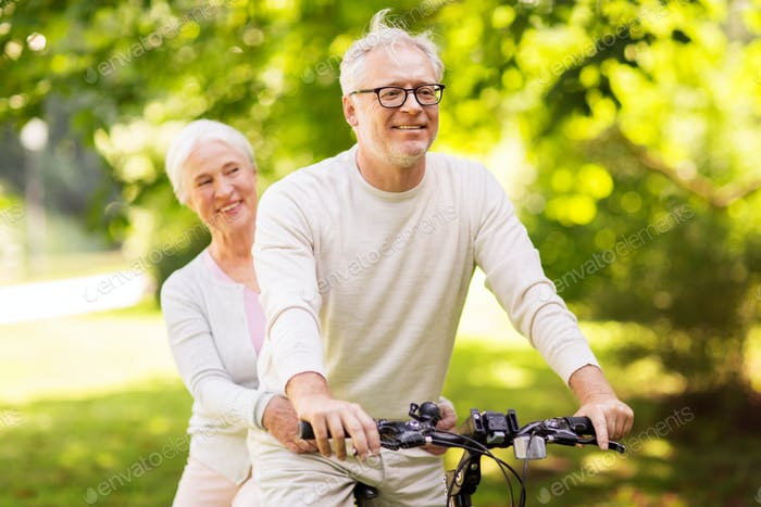 happy senior couple riding bicycle at park