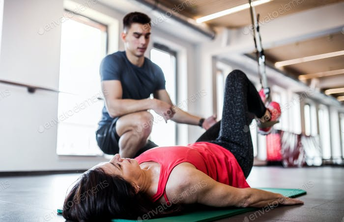 A senior woman in gym and a personal trainer doing exercise with TRX.
